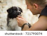Stock photo happy young man holding and looking at amazing cute border collie puppy 721793074