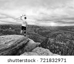 Small photo of Happy man hiker holding medicine crutch above head, injured knee fixed in knee brace feature. Scenic mountain top with deep misty valley bellow