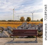 Small photo of Empty wooden bench at park with beautiful background and wind turbine for green alternative energy