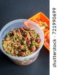 Small photo of Rice with red beans and chicharron pieces in a plastic cup accompanied with tomato and crushed onion.