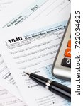 tax form with pen and calculator | Shutterstock . vector #722034625