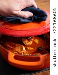 Small photo of Man lifting lid on a chicken paprika casserole