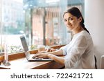 upbeat woman typing on laptop... | Shutterstock . vector #722421721