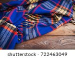 Small photo of Blue plaid plaid bedspread on a wooden table