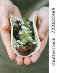 Small photo of Steak taco with toppings being being help between two hands