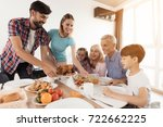 Small photo of The family sits down for dinner on Thanksgiving. The man serves a festive turkey, his wife stands beside him and serves a salad, the rest sit and look forward to
