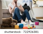 Small photo of Overwhelmed exhausted woman feeling tired of cleaning in her messy house sitting on the floor with toys and laundry lying around her