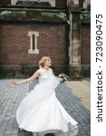 Small photo of Funny bride stands against the wind