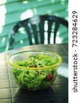 Small photo of Salad bowl on a plastic garden table outside