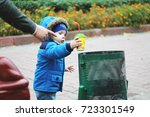 Small photo of A small child in the street throws a paper glass in the trash can. His dad points with his finger where to throw garbage. The concept of a clean planet. Parents teach children purity