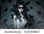 Small photo of Little santa muerte girl with black curly hair dressed in white as the halloween character