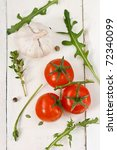 Tomatoes, arugola, garlic and thyme on a white wooden boards. - stock photo