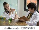 Two Hispanic Scientist Mixing...