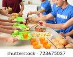 volunteers serving food for... | Shutterstock . vector #723675037