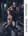 trainer helping woman to... | Shutterstock . vector #723702265
