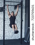Small photo of young man in sportswear doing pull ups on pull up bar in gym