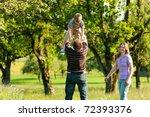 family having a walk outdoors... | Shutterstock . vector #72393376