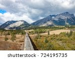 Overhead View of Grain Cars Stretching toward  Mountains (horizontal) - stock photo