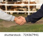 Small photo of Two farmers shaking hands in front of cow ranch. Agribusiness concept