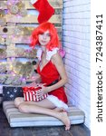 Small photo of Girl with serious face dressed like Santa. Lady holds Christmas striped present box with red bow. Woman sits on pillow against decorated wall. Holidays and presents concept.