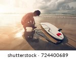 woman surfer tying leash of the ... | Shutterstock . vector #724400689