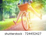 woman riding bicycle with her... | Shutterstock . vector #724452427