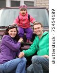 Small photo of Happy family in outwear - mother and father hunker down in front of car and support little daughter sitting on car