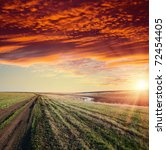 red sunset over river and rural road with dramatic sky - stock photo