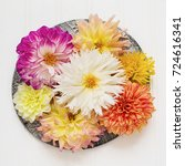 Small photo of Various types of dahlias arranged on a pewter colored plate.