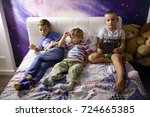 brothers watching tv on sofa at ... | Shutterstock . vector #724665385