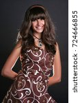 Small photo of Beautiful girl with bangs in a long brown dress stands isolated on a black background