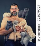 Stock photo man holding many kittens 725079727