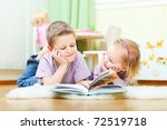 Cute boy and his little sister at home reading - stock photo