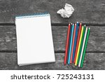 Small photo of Notepad with blank sheet of paper, colored pencils and crumpled sheet of paper on the old wooden background. Workplace of the artist, writer. Never give up.