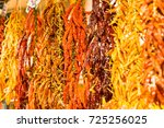 Small photo of Assorted colorful varieties of hot and sweet dry peppers in the market. Rows of variety chili peppers hang together in bunches at market stall. Different forms, different colors. God for background