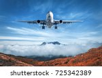 airplane is flying over low... | Shutterstock . vector #725342389