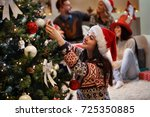 woman decorates christmas tree... | Shutterstock . vector #725350885