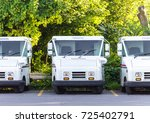 Small photo of Three Empty, Parked, United States Post Office Trucks Lined up in a Row in a Parking Lot, Exterior, Evening Sunlight, Medium Shot, Eye Level, Trees in Background.