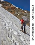 Small photo of Alpinist climbing a mountain with snow field