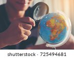 Small photo of Young businessmen are looking through a magnifying glass to the globe to find a target audience. Look for or find a business target (concept)