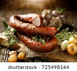 smoked sausage on a wooden... | Shutterstock . vector #725498164