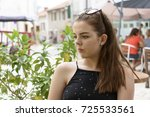 Young woman, relaxing in the sunshine at a table outside a cafe in in Aubeterre-sur-Dronne, France - stock photo