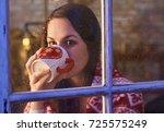 pretty woman in warm room... | Shutterstock . vector #725575249