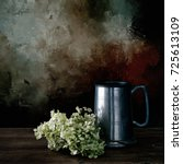 Small photo of Vintage pewter tankard with dried hydrangea flowers. Still life. Digitally enhanced and filtered photo.