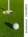 Small photo of Golf ball on the green course. Close up. Sport, relax, recreation and leisure concept