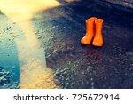 orange rubber boots standing... | Shutterstock . vector #725672914
