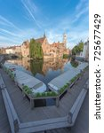 Small photo of Pictoresque famous canal corner in Bruges, Brugge, Belgium. Wide angle view with boats docked and almost ready to start the daily routes across the beautiful canals of the Venice of the North.