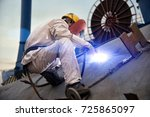 a welder in a shipyard | Shutterstock . vector #725865097
