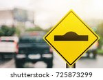 Small photo of Hump warning sign on blur traffic road with colorful bokeh light abstract background. Copy space of transportation and travel concept. Retro tone filter effect color style.