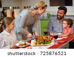 female serving roasted turkey... | Shutterstock . vector #725876521